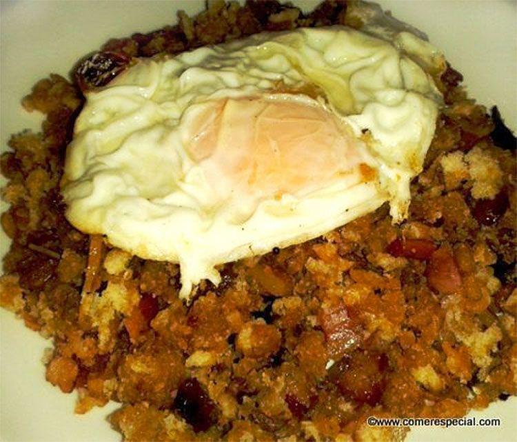 Migas con jamón serrano, beicon, pasas y huevo frito